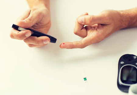 hyperglycemia: close up of man checking blood sugar by glucometer