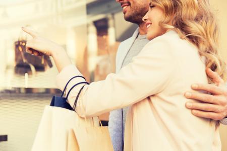 Paar mit Einkaufstüten im Schaufenster suchen Standard-Bild - 71052442