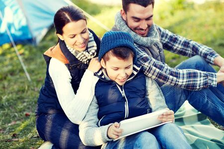 campsite: happy family with tablet pc and tent at camp site