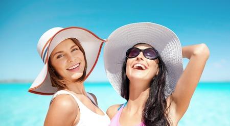 glückliche junge Frauen in den Hüten auf Sommerstrand