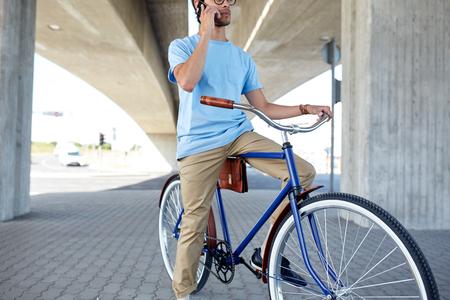 fixed: el hombre con el teléfono inteligente y la bicicleta fija del engranaje en la calle