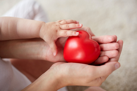 close up of baby and mother hands with red heart