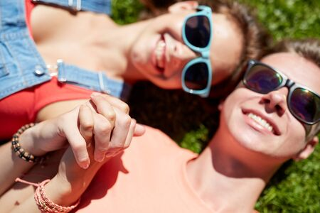 happy teenage couple lying on grass at summer Stock Photo
