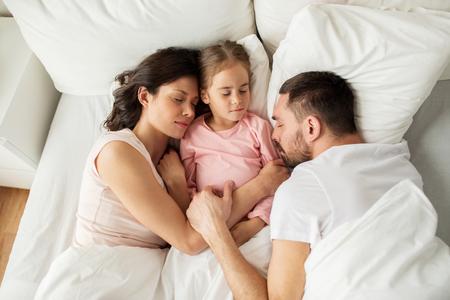 mom dad: dormir de la familia feliz en la cama en su casa