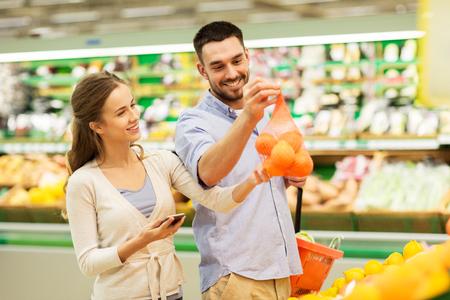 Paar mit Smartphone kaufen Orangen auf Lebensmittelgeschäft