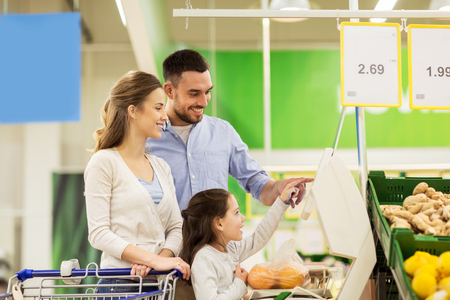 family weighing oranges on scale at grocery store