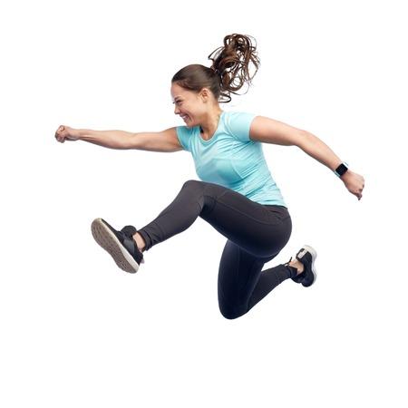 空気中のジャンプ スポーティな若い女性の幸せな笑顔