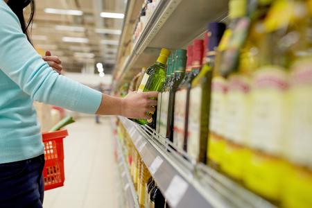 donna che compra l'olio d'oliva al supermercato o alla drogheria Archivio Fotografico