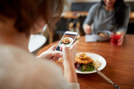 women with smartphones and food at restaurant
