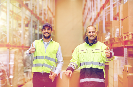 men with boxes showing thumbs up at warehouse