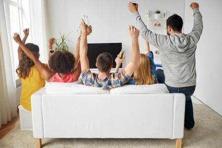 gelukkige vrienden met bier op TV thuis