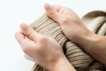 close up of hands with knitted clothing item Stock Photo