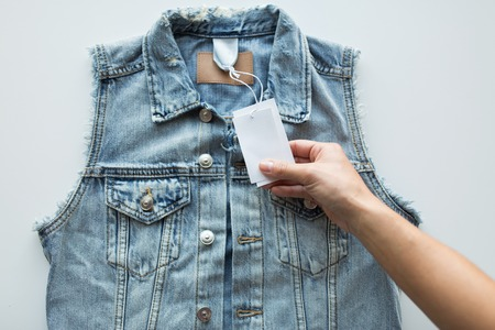 docket: close up of hand holding price tag of denim vest