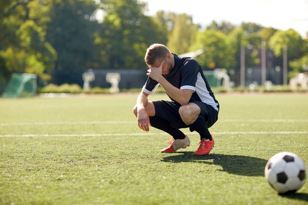 sad soccer player with ball on football field