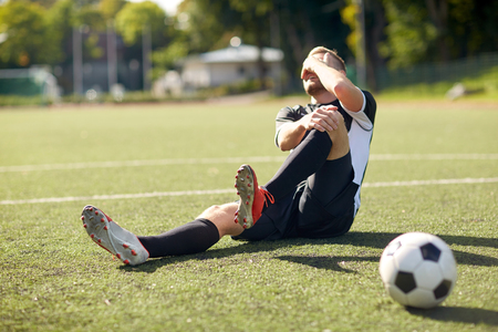 injured soccer player with ball on football field Stock Photo