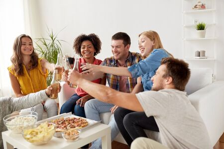 alcohol drinks: friends having party and clinking drinks at home