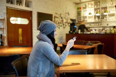 mobile app: young woman with smartphone at cafe