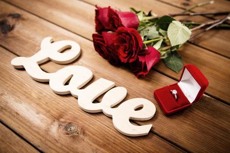 propozycja, romans, walentynki i święta koncepcji - zamknąć pudełko z romb pierścionek zaręczynowy, czerwone róże i słowo miłość na drewno (vintage effect) Zdjęcie Seryjne