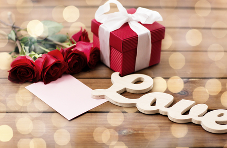 uprzejmości: love, romance, valentines day and holidays concept - close up of gift box, red roses and greeting card with heart on wood (vintage effect)