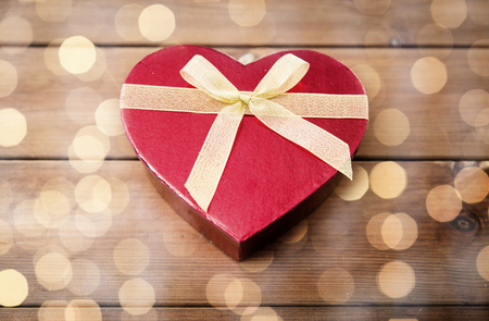 attentions: close up of heart shaped gift box on wood