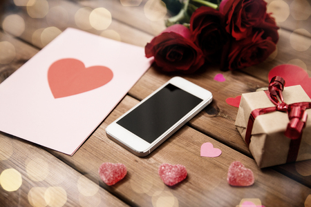 attentions: close up of smartphone, gift, red roses and hearts