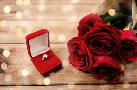 attentions: close up of diamond engagement ring and red roses Stock Photo