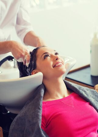 shampooing: happy young woman at hair salon Stock Photo