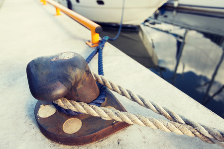 pawl: rusted iron mooring bollard with rope on pier Stock Photo