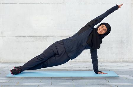 Sport, Eignung und Leutekonzept - glückliche lächelnde moslemische Frau im hijab, das Plankenübung auf Matte über grauem Betonmauerhintergrund tut Standard-Bild - 70993413
