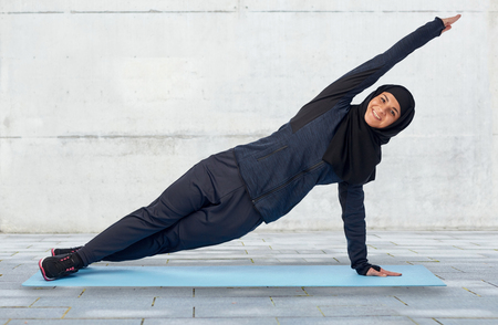sport, fitness and people concept - happy smiling muslim woman in hijab doing plank exercise on mat over gray concrete wall background Фото со стока