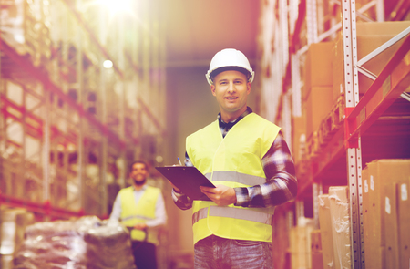 wholesale, logistic, people and export concept - man with clipboard in reflective safety vest at warehouse Stock Photo - 70992574