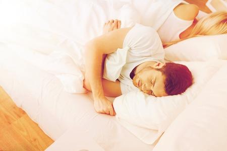 gente durmiendo: la gente, las dificultades de relación, conflictos y concepto de familia - pareja durmiendo de espaldas en la cama en su casa Foto de archivo