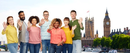 british ethnicity: travel, tourism, diversity, ethnicity and people concept - international group of happy smiling men and women waving hand over london city background Stock Photo