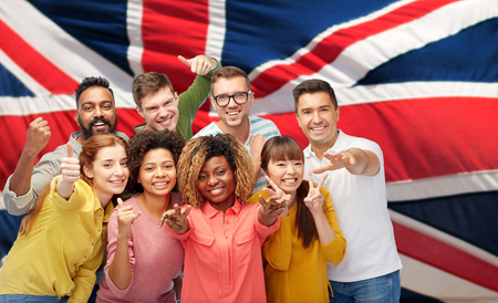 diversity, race, ethnicity and people concept - international group of happy smiling men and women showing thumbs up and peace over british or english flag background