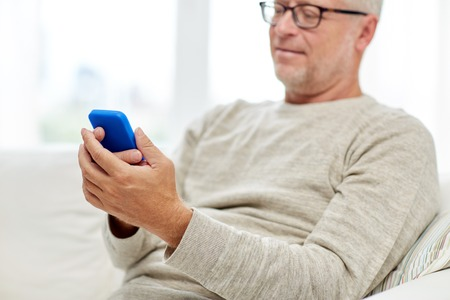 close up of senior man with smartphone at home Stockfoto