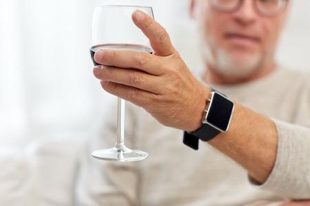 puntualidad: hombre mayor de beber vino tinto de vidrio en el hogar
