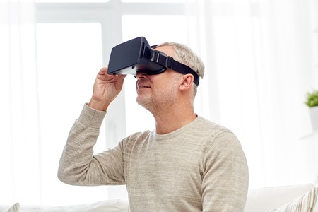 mediated: technology, augmented reality, gaming, entertainment and people concept - senior man with virtual headset or 3d glasses playing videogame at home Stock Photo