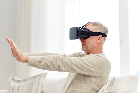 technology, augmented reality, gaming, entertainment and people concept - senior man with virtual headset or 3d glasses playing videogame at home Stock Photo