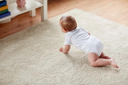 babyhood: childhood, babyhood and people concept - little baby boy or girl crawling on floor at home Stock Photo