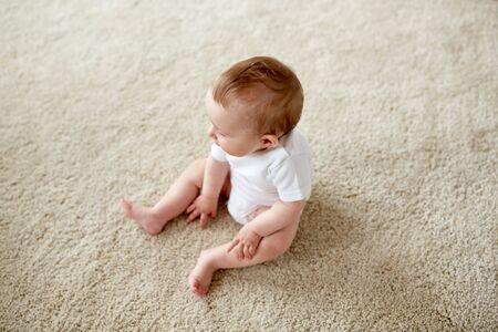 乳幼児: 幼年期、乳児および人々 のコンセプト - 幸せな赤ちゃん男の子か女の子の自宅の床に座って