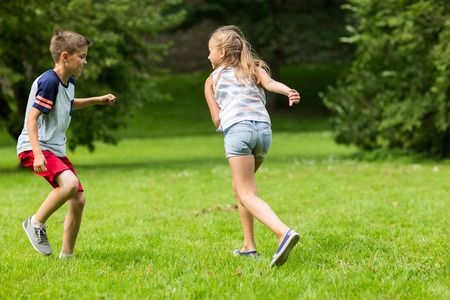 friendship, childhood, leisure and people concept - group of happy kids or friends playing catch-up game and running in summer park Reklamní fotografie