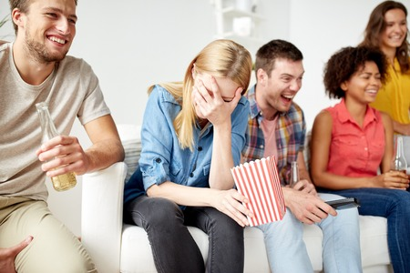 alcohol drinks: happy friends with popcorn and beer at home Stock Photo