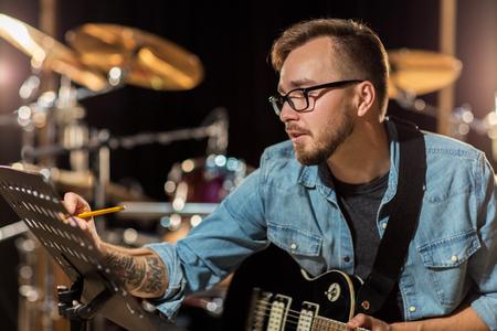 music lyrics: el hombre con la escritura guitarra para el libro de música en el estudio