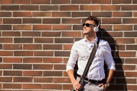 personas escuchando: estilo, la música, la tecnología y el concepto de la gente - hombre joven y sonriente feliz en auriculares y gafas de sol con bolsa en la pared de ladrillo