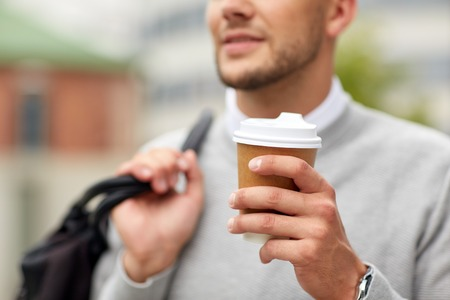 people, drinks and lifestyle - close up of man drinking coffee from disposable paper cup on city street