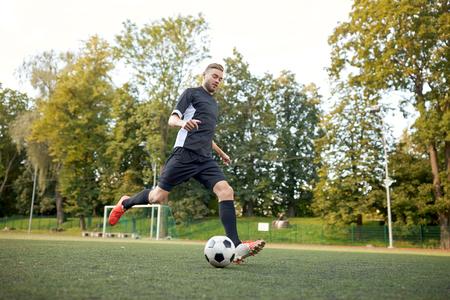 voetballer spelen met bal op voetbalveld