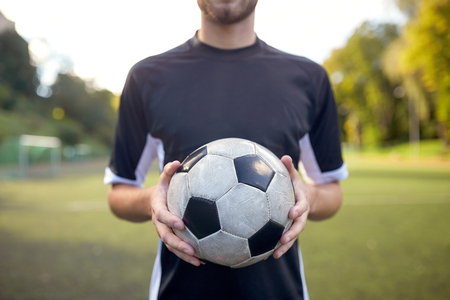competitive sport: close up of soccer player with football on field Stock Photo