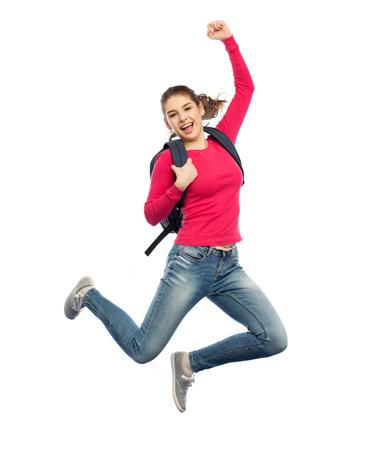 Bildung, Reise, Tourismus, Bewegung und Leutekonzept - lächelnde junge Frau oder Student mit dem Rucksack, der in einer Luft über weißem Hintergrund springt Standard-Bild - 70994473