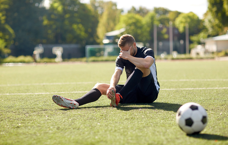 injured soccer player with ball on football field Standard-Bild