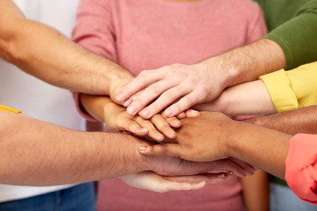 all in one: group of international people with hands together